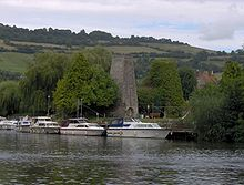 Looking across water to moored boats. Beyond them is a stone chimney surrounded by trees, with hills in the distance.