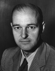 Head and shoulders portrait of a balding man, wearing a suit and tie.