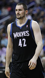 """A basketball player, wearing a black jersey inscribed with the word """"WOLVES"""" and the number 42 on the front."""