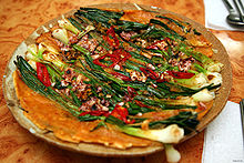 A plate of a colorful pancake made with green scallions, sliced red chili pepper and chopped seafood
