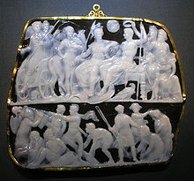 A photograph showing a roughly rectangular gem set in a gold frame with 2 carved panels with various figures carved in shallow from translucent white chalcedony against a solid black background