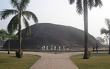 A very large hill behind two palm trees and a boulevard, people walking are about one fifth the hill's height