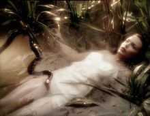 The body of a woman in a white dress floats on her back in a pond. Her body is submerged, and only her face, with open eyes, is above the water. There are plants near her, and a black snake swims through the water, its head over the top of her exposed thigh.