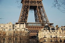 photographie du bas de la tour Eiffel avec quelques immeubles en premier plan