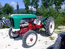 A green and red tractor parked in a gravel patch with trees and hills in the background