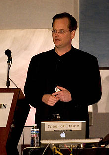 Lawrence Lessig standing at a podium with a microphone, with a laptop computer in front of him.