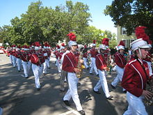 Several rows of high schoolers holding musical instruments walk along a residential street.