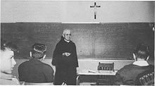 Three young men listen as an elderly monk gives a lecture in front of a chalkboard, a desk with a chair, and a crucifix.