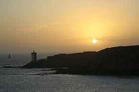 Silhouette de la presqu'île et du phare de Kermorvan lors d'un coucher de soleil.