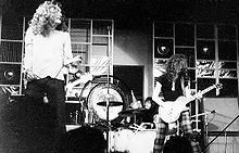 A black and white photograph of Robert Plant performing with microphone stand and Jimmy Page with guitar