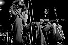 A black and white photograph of Robert Plant with a tambourine and Jimmy Page with an acoustic guitar seated and performing