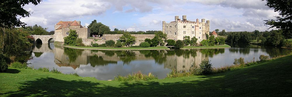 A castle on two islands surrounded by a lake. A stone curtain wall runs along the edge of the first island and access is provided by a stone bridge and gatehouse. The second island has a square stone keep.