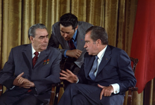 Two older men in suits sit next to each other, while a third stands behind leaning in to listen to the right man talk.