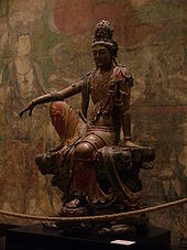 A wooden carving of a sitting Buddhist figure in loose fitting, painted robes.