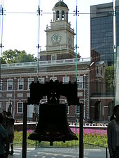 The Liberty Bell hangs in a glass-backed structure, with a brick, 18th century building with a steeple visible in the background.