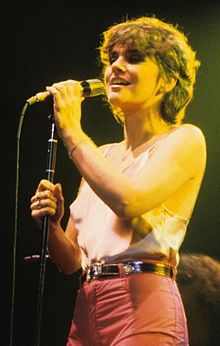 Ronstadt, in her early to mid-30s, is singing at a concert dressed in a light pink silk camisole top and light red pants with medium-length hair, clutching a microphone on a stand with both hands.
