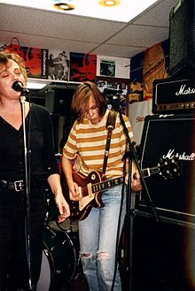 Linda Hopper stands behind a microphone singing with Ruthie Morris to her left playing guitar in front of a stack of Marshall Amps