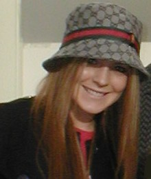 A red-haired white female wearing a black coat and a hat