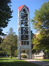 A three-dimensional vertical structure perhaps 70 feet (21m) tall and 10 feet (3.0m) wide by 10 feet (3.0m) long is filled with tiers of large metal bells. The structure, standing in front of a large institutional building in a park-like setting, is supported by several metal legs. A sidewalk passes through the structure, which is open at the bottom to a height of perhaps 10 feet (3.0m).
