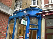 """A building painted blue, with a sign reading """"The Glass House"""". An advertisement on glasses is affixed on the door."""