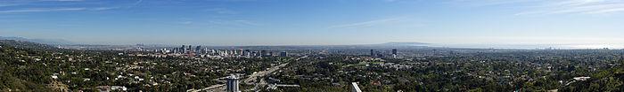 Photo en couleur, prise d'un point élevé, de Los Angeles; on voit la ville au loin, au premier plan il y a de nombreux espaces verts arborés.