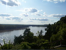 A wide river flows between dark forests and low bluffs