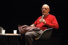 Le cinéaste Luc Moullet en 2008 à la cinémathèque française, il est vêtu d'un pull rouge et d'un pantalon gris. Il parle dans un micro pour se faire entendre du public.