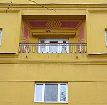 Portion of yellow apartment house with small balcony