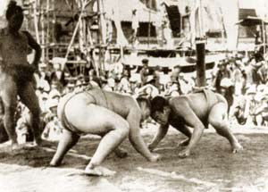 Two sumo wrestlers confront each other on a platform, their heads touching and their fists on the ground. To the side, a third man, also in a wrestling outfit, looks on. In the background, a crowd watches.