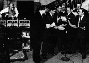 Seven suited men holding scripts and an eighth man operating a bank of turntables.