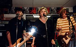 Magnapop performing in a record store with flyers for their album tacked on the wall behind them