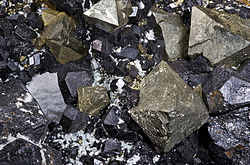 Magnetite exposed on the ground. The mineral is black and irregularly smooth. Individual chunks jut at angles characteristic of the crystal habit.