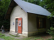 A small grey hut, surrounded by woods, with an open door to which is affixed a picture of the composer