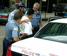 three police officers surround a man in a tee shirt who is handcuffed