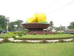 """Photo of painted """"sculpture"""" of mango at the center of a road roundabout"""