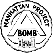 "Circular shaped emblem with the words ""Manhattan Project"" at the top, and a large ""A"" in the center with the word ""bomb"" below it, surmounting the US Army Corps of Engineers&squot; castle emblem"