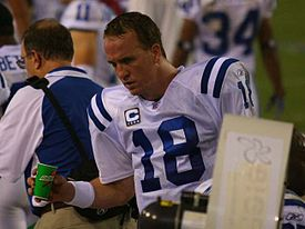 "A man holding a green paper cup. He is wearing a white jersey with blue stripes and a blue ""18"" on the front, which also has a logo with a white ""C"" above one gold and three white stars. Other men wearing white jerseys with blue numbers and names are visible in the background."