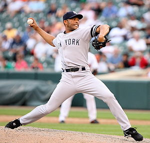 "A right-handed Hispanic baseball pitcher, wearing a grey uniform with the lettering ""NEW YORK"" across it, with his body facing the image, in his throwing stance."