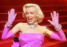 Bust of a blond woman in short curled hair and wearing a bright pink, sleeveless dress. Putting both her hands up, she looks to the right of the image.