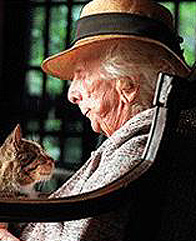 A color photograph of Marjory Stoneman Douglas late in her life. She is shown in profile, seated, with a cat on her lap. She is white-haired tanned and wrinkled. She wears a lapelled jacket and low-brimmed straw hat. She and the cat gaze at each other lovingly.