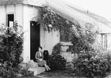 Photograph of Douglas, in her thirties, elegantly dressed, seated on a step outside a cottage which has a low roofline and is surrounded by a profusion of plants.