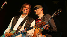 Mark Tulin—a middle-aged Caucasian male with long brown hair wearing a white shirt and black vest—plays bass guitar and smiles while Billy Corgan—a middle-aged Caucasian male wearing a dark green hat and red-and-black striped shirt with a brown jacket—plays electric guitar to his left.