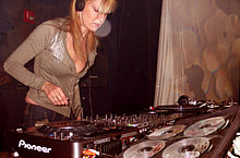 Long-haired, blonde female in low cut sweater and low cut jeans wearing earphones, stands before a studio sound board adjusting the switches.