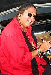 A woman wearing sunglasses and a red jacket signing a compact disc