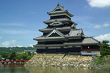 A large five-story castle tower with black wooden walls located on a platform of unhewn stones surrounded on two sides by water. The tower is connected to the lower structure.