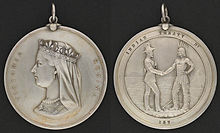 "Two sides of a silver medal: the profile of Queen Victoria and the inscription ""Victoria Regina"" on one side, a man in European garb shaking hands with an Aboriginal with the inscription ""Indian Treaty 187"" on the other"