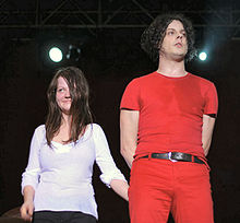 The White Stripes standing on stage: Meg White is to the left, wearing a white shirt and black pants, smiling at the crowd; to her left is Jack White wearing a red outfit with a black belt