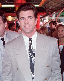 A man in a grey suit. Behind him is a small crowd of people.