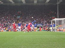 People in blue and red shirts on a field with a ball in the air. In the background is a stand that contains a lot of people.