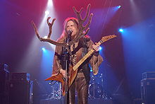 Long-haired man in beige shirt with wide sleeves and a brown leather vest and pants, plays the electric guitar on stage and sings. There is a large pair of felt antlers pinned to the microphone.